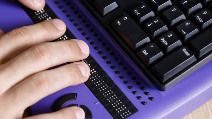 A hand is placed on top of a laptop, just below the keyboard where braille is located. The laptop is purple with black keyboard keys.