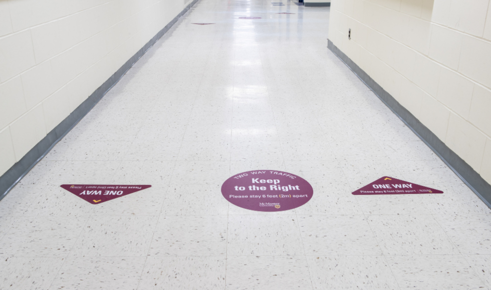 Social distancing signage on the floor of a building at McMaster University.
